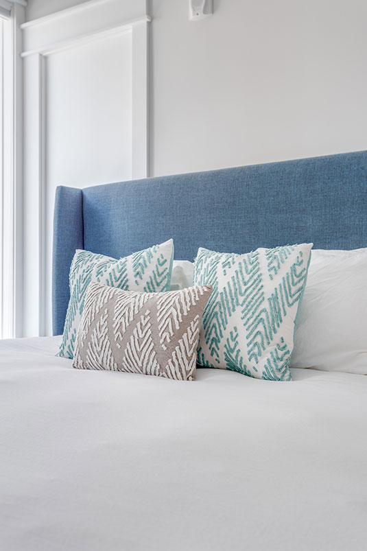 Bed with blue headboard and modern pillows