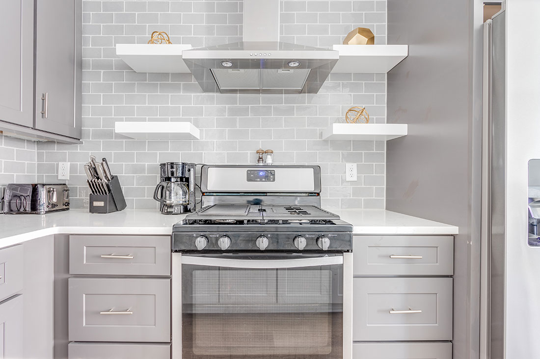 stainless steel appliances in modern kitchen with bright shelving and gray backsplash