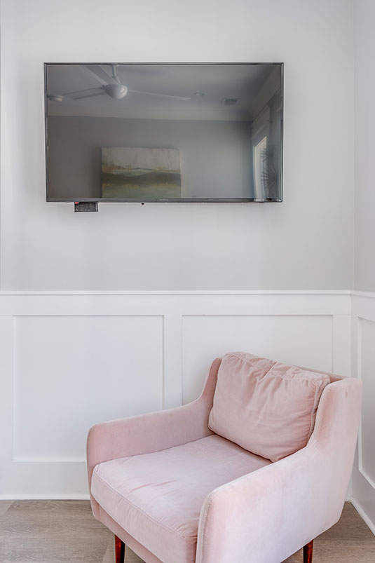 pink chair in front of a bright wall with a tv above