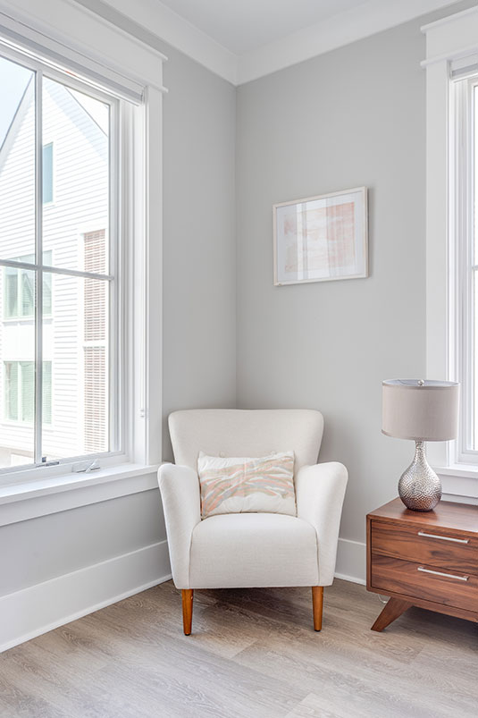 White bedroom chair against gray wall in bright room